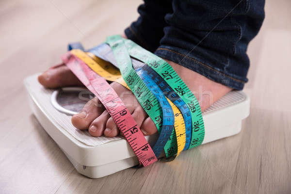 Person's Feet On Weight Scale Wrapped With Measuring Tape Stock photo © AndreyPopov