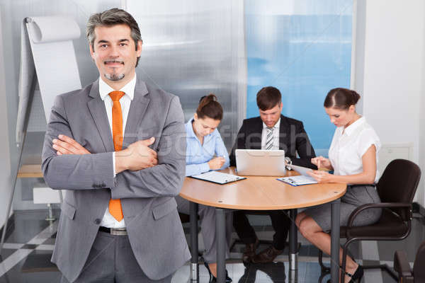 Stock photo: Businessman With Arm Crossed Standing In Front Of His Colleagues