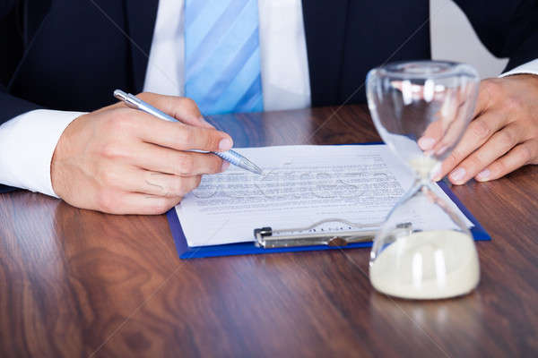 Businessman Filling Form In Front Of Hourglass Stock photo © AndreyPopov
