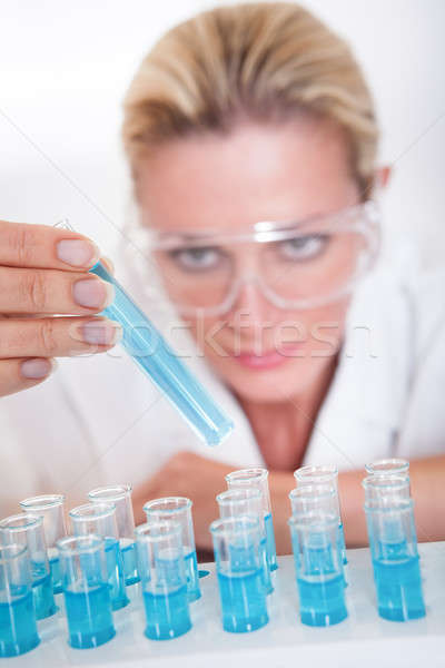 Lab technician woman looking at testubes Stock photo © AndreyPopov