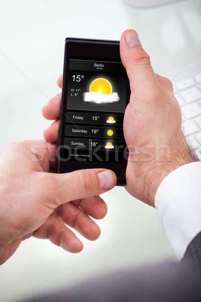 Empresario mirando tiempo pronóstico teléfono celular primer plano Foto stock © AndreyPopov