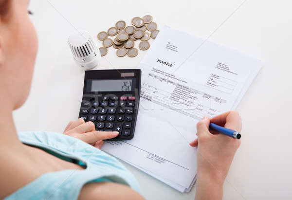 Woman Calculating Invoice At Desk Stock photo © AndreyPopov
