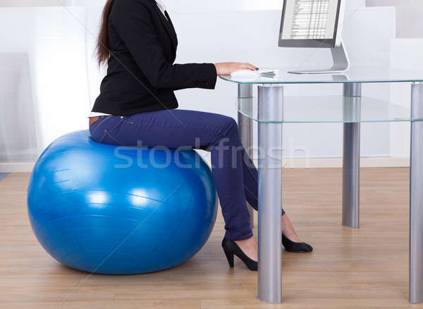 Businesswoman Working While Sitting On Pilates Ball Stock photo © AndreyPopov