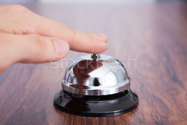 Hand Ringing Service Bell Kept On Wooden Table Stock photo © AndreyPopov