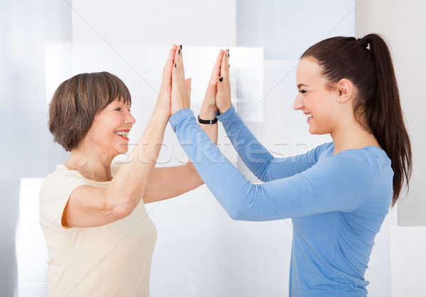 Caregiver And Senior Woman Giving High Five Stock photo © AndreyPopov