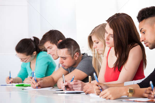 Stock photo: Row Of College Students Writing At Desk