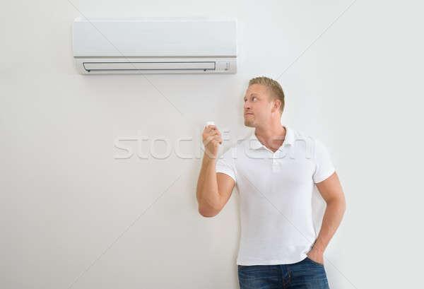 Hombre acondicionador de aire control remoto retrato remoto pared Foto stock © AndreyPopov