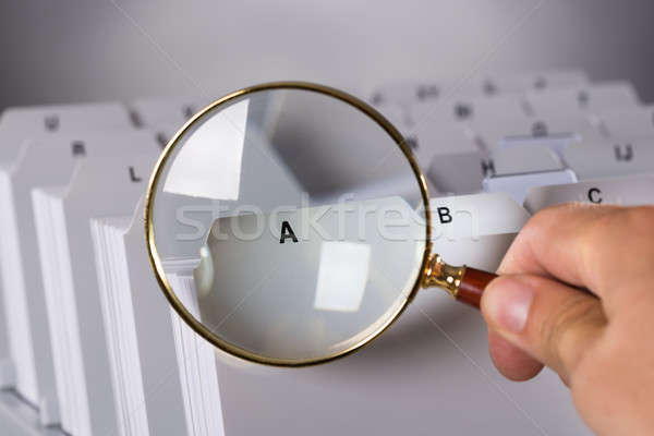 Investigating documents with magnifying glass Stock photo © AndreyPopov