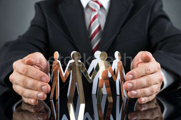 Businessperson Protecting Cutout Figures Stock photo © AndreyPopov