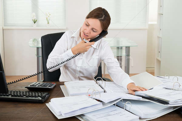 Businesswoman Using Telephone While Doing Accounting Stock photo © AndreyPopov