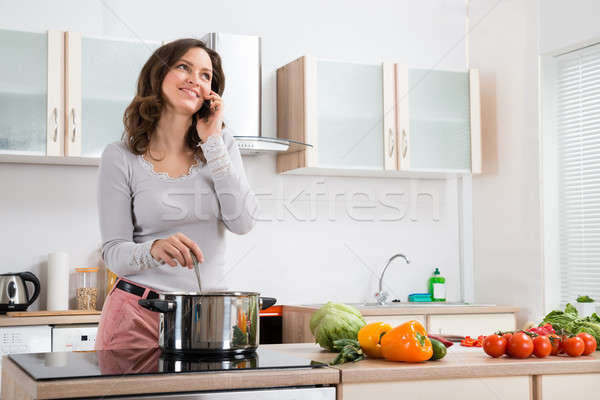 Woman With Mobile Phone While Cooking Stock photo © AndreyPopov