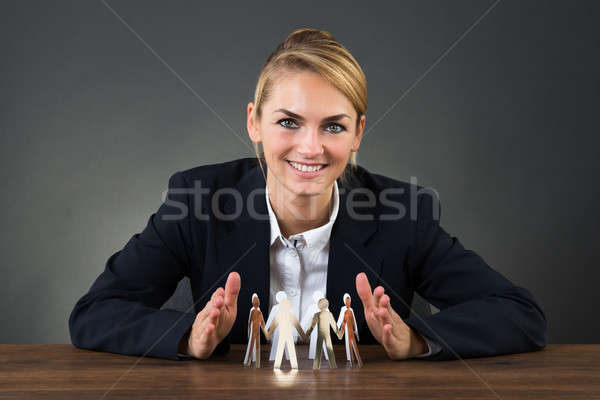 Businesswoman Sheltering Paper Team On Desk Stock photo © AndreyPopov