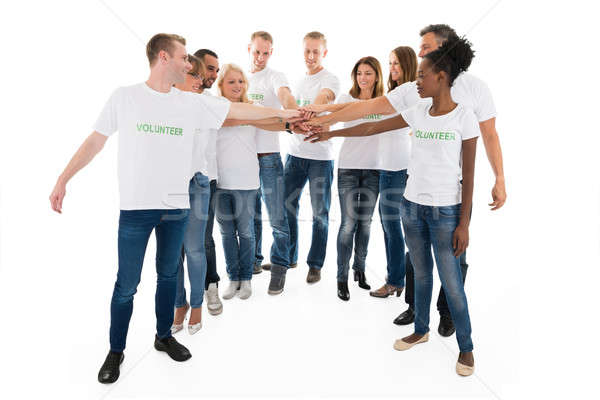 Multiethnic Volunteers Stacking Hands Against White Background Stock photo © AndreyPopov