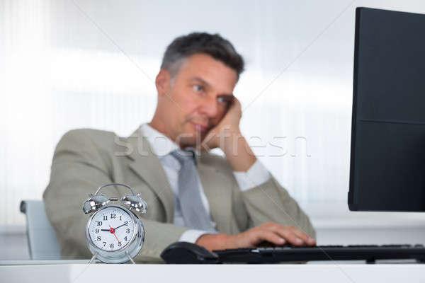 Businessman Using Computer At Desk With Focus On Clock Stock photo © AndreyPopov