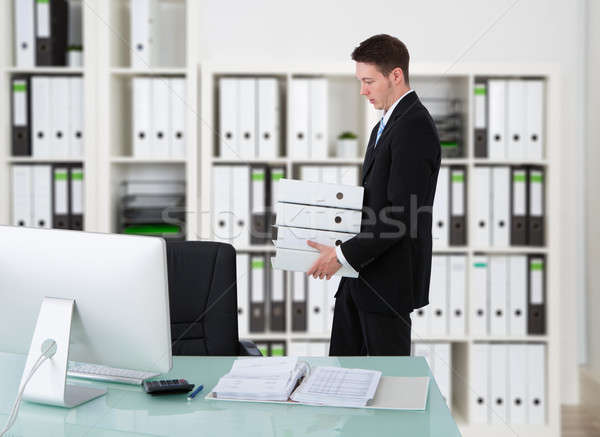 Businessman Carrying Binders By Desk Stock photo © AndreyPopov