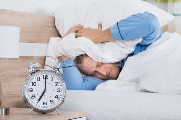 Sleeping Man Disturbed By Ringing Alarm Clock Stock photo © AndreyPopov