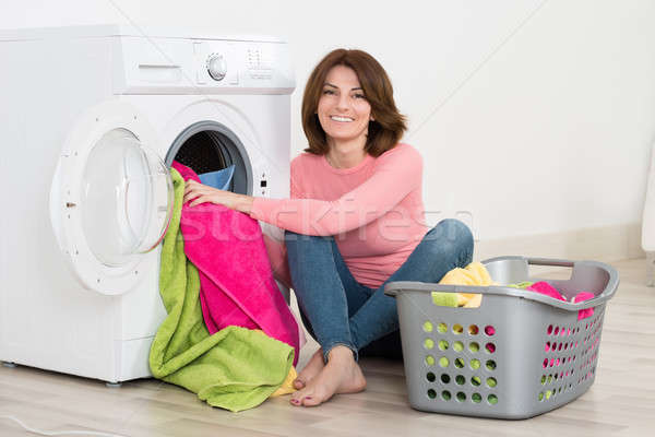 Happy Woman Putting Clothes Into Washing Machine Stock photo © AndreyPopov
