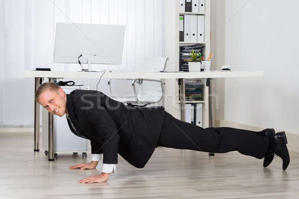 Businessman Doing Pushup At Work Stock photo © AndreyPopov
