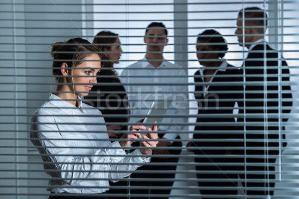 Zakenvrouw digitale tablet permanente achter blinde Stockfoto © AndreyPopov