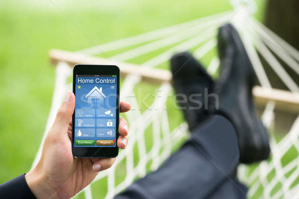 Man With Mobile Phone Showing Home Control System Stock photo © AndreyPopov