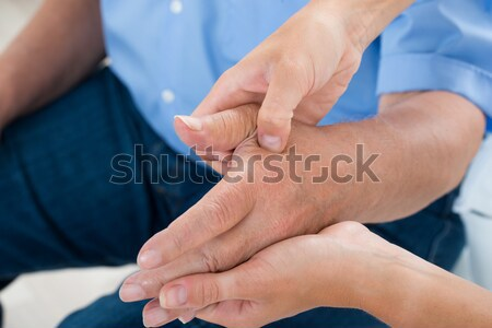Physiotherapist Massaging Palm Of A Man Stock photo © AndreyPopov