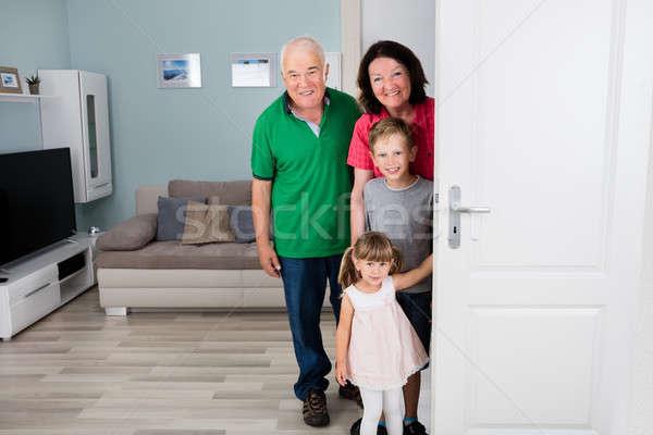 Grandparent And Grandchildren Standing Behind Door Stock photo © AndreyPopov