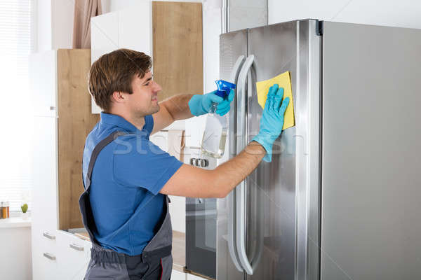 Man Cleaning Stainless Refrigerator Stock photo © AndreyPopov