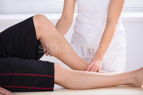 Physiotherapist Giving Knee Therapy In Clinic Stock photo © AndreyPopov