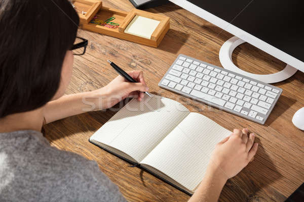 Woman Writing On Checker Note Book Stock photo © AndreyPopov