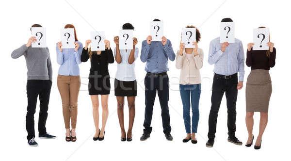 Grupo universidad estudiantes ocultación detrás signo de interrogación Foto stock © AndreyPopov