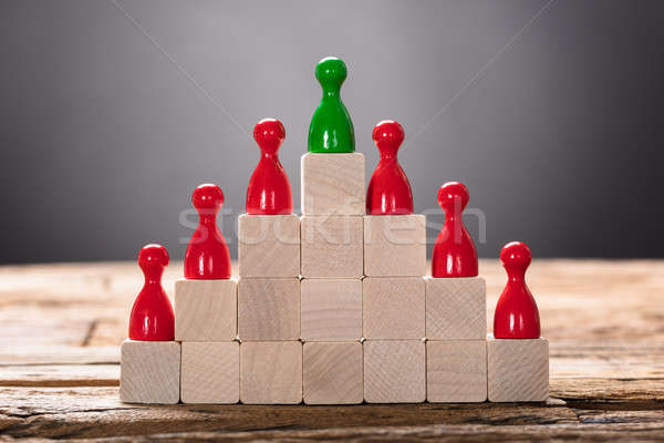 Green And Red Pawn Figurines Arranged On Wooden Blocks Stock photo © AndreyPopov