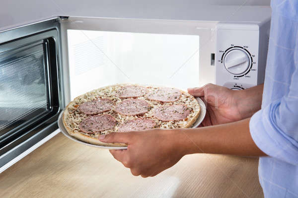 Persoon salami pizza magnetronoven oven Stockfoto © AndreyPopov