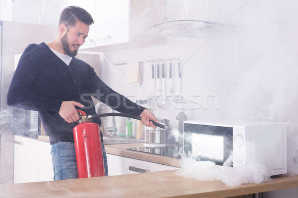 Man Spraying Fire Extinguisher On Microwave Oven Stock photo © AndreyPopov