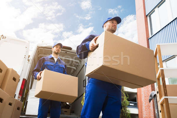Stock photo: Close-up Of Two Delivery Men Carrying Cardboard Box