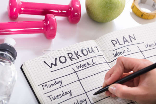 Workout Plan In Notebook At Wooden Desk Stock photo © AndreyPopov