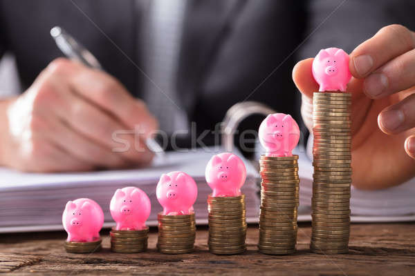 Businessperson Placing Piggybank On Stacked Coins Stock photo © AndreyPopov
