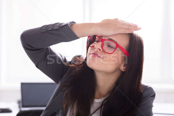 Businesswoman With Her Hand On Forehead Stock photo © AndreyPopov