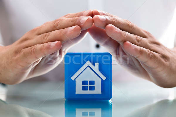 Person protecting cubic block with house icon Stock photo © AndreyPopov