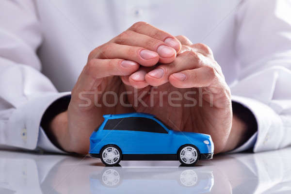 Businessman Protecting Blue Car Stock photo © AndreyPopov