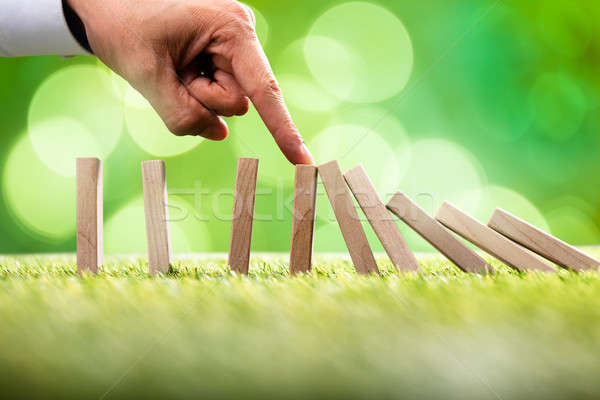 Person Stopping Falling Wooden Blocks Stock photo © AndreyPopov