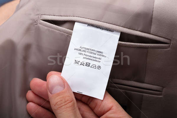 Man Holding Trouser Label Showing Caution Tag Stock photo © AndreyPopov