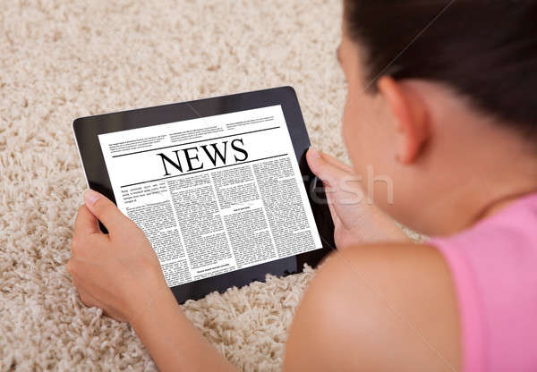 Young Woman Reading A News Article On Digital Tablet  Stock photo © AndreyPopov