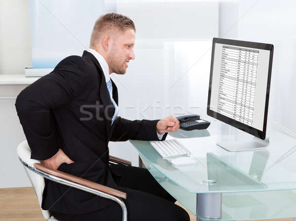 Businessman rubbing his back as he sits working at his desk Stock photo © AndreyPopov