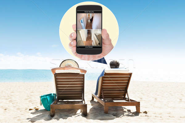 Hombre esposa mirando seguridad teléfono móvil playa Foto stock © AndreyPopov