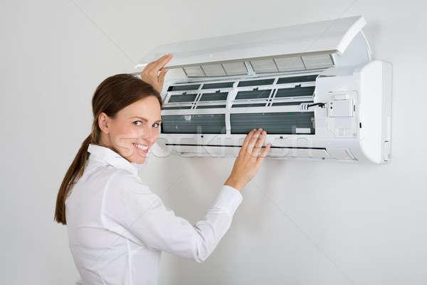 Mujer de negocios acondicionador de aire jóvenes pared oficina negocios Foto stock © AndreyPopov