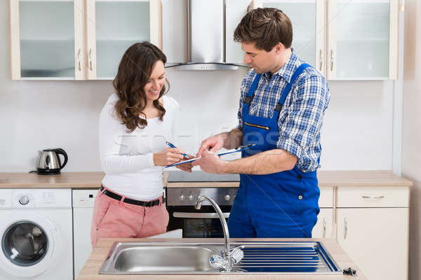 Woman Writing On Clipboard With Plumber In Kitchen Room Stock photo © AndreyPopov