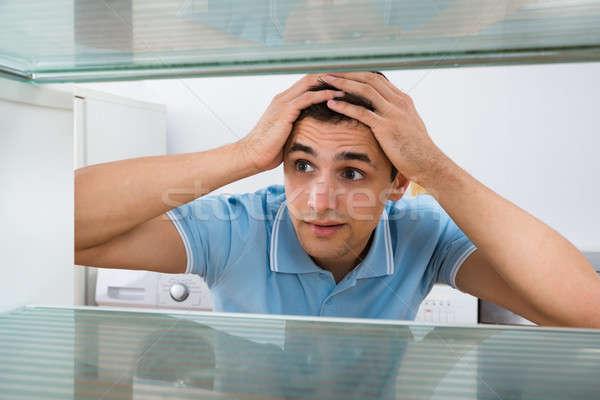 Amazed Man Looking Into Empty Refrigerator Stock photo © AndreyPopov