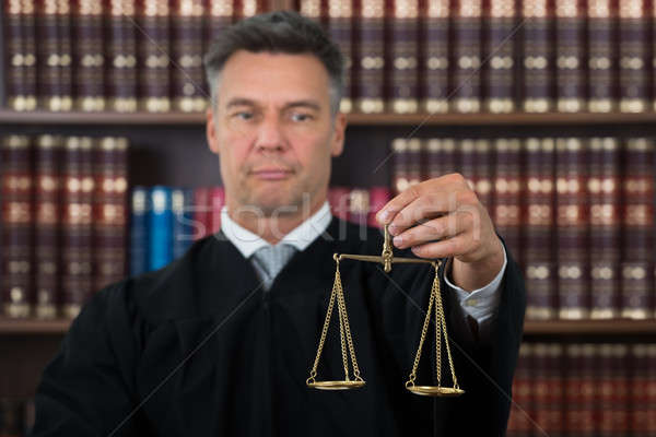 Judge Holding Justice Scale In Courtroom Stock photo © AndreyPopov