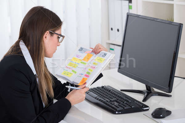 Businesswoman Looking At Her Diary Stock photo © AndreyPopov
