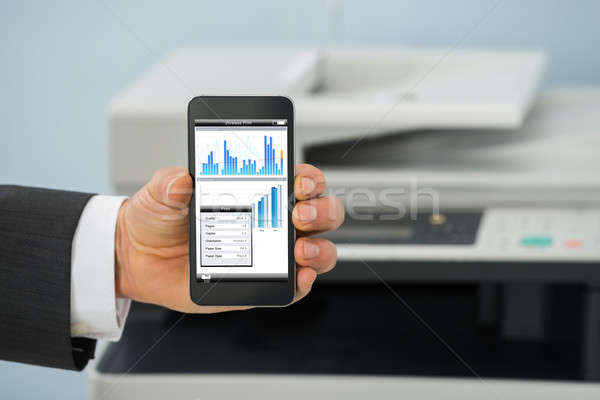 Businessman Using Cellphone For Printing Graph Paper Stock photo © AndreyPopov